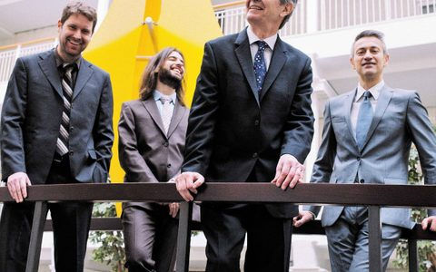 four musicians smiling and in suits standing outside