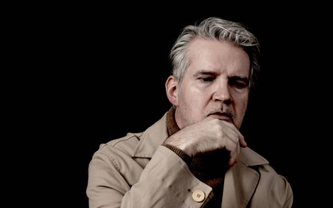 Man looking down wearing a trench coat and looking pensive