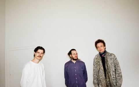 Three men against a cream wall wearing shirts and leopard print