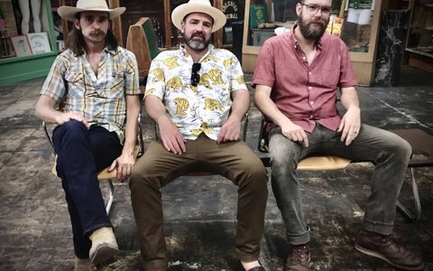Three men in chairs outside in floral shirts and wearing hats