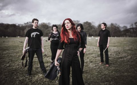 Five musicians stood in a field all wearing black with a woman in the foreground with striking red hair