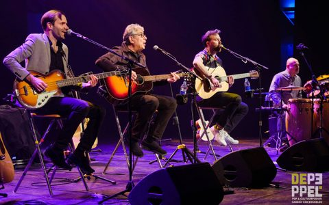 four men sat on stools on stage playing instruments in a line under purple lighting