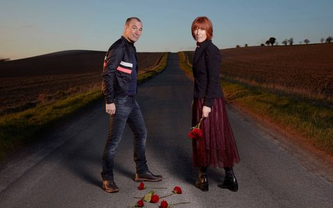 Man and woman stood on an empty road holding a rose and with other roses laid on the floor