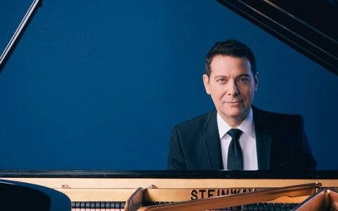 Man in a suit smiling sat at a piano in front of a blue screen