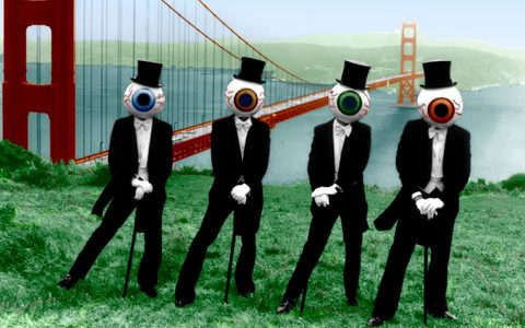 Four men in tuxedo's and cane's with eyeball masks covering their heads and in front of the golden gate bridge