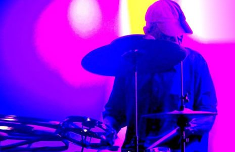 Man playing drums in a pink wash lighting