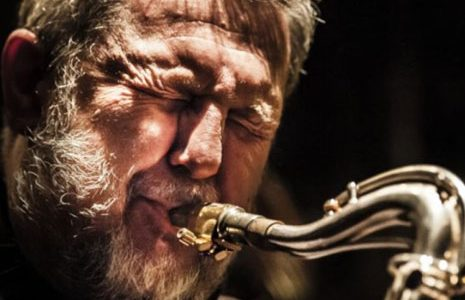 Man playing the saxophone with expressive face