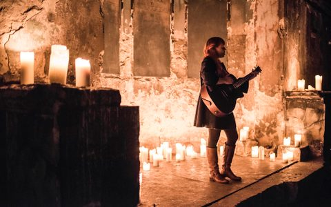A woman playing guitar on a dramatic stage filled with candles
