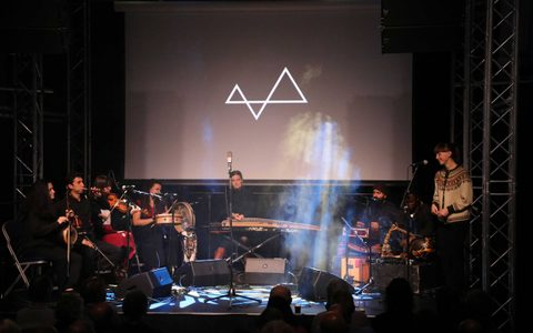 Musicians performing on stage underneath a large projector with a symbol on