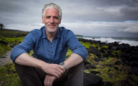 Man with short silver curly hair sat on the floor and smiling near the crashing waves off the shore
