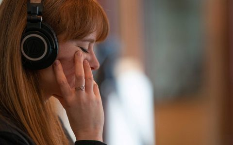 Side profile of a woman with red hair listening to headphones and holding her head in her right hand in front of a blurry backround
