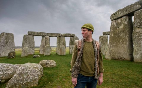 man wearing a beanie hat and casual waistcoat stood in the middle of stonehenge