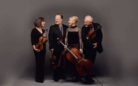 four smartly dressed musicians stood together and looking at each other wearing black and holding their instruments