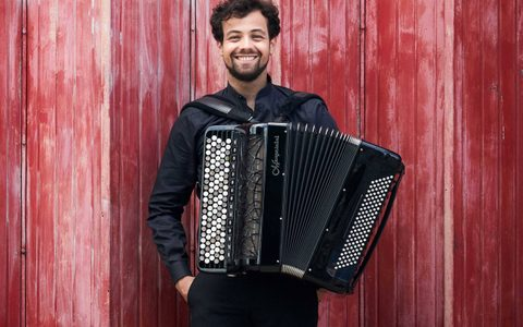 Man with an accordion strapped to him wearing a black shirt and smiling