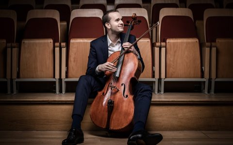 Man wearing a suit and smiling holding a cello in front of auditorium seating