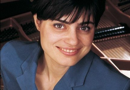 Woman with a fringe smiling wearing a blue short in front of a piano