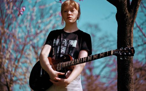 Girl wearing a black tshirt stood with an electric guitar in front of trees