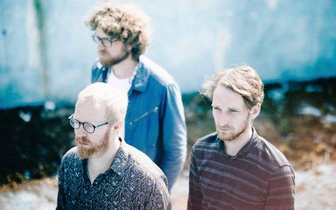 Three men walking in a triangle outside