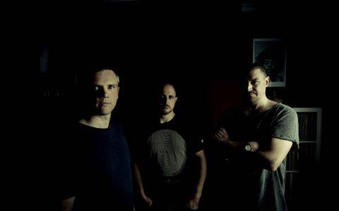 Three men in a dark room
