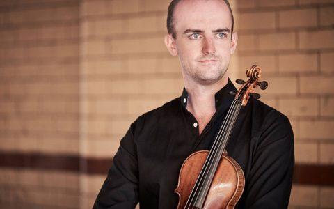 man in black shirt holding a violin